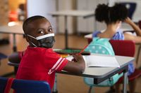 Portrait of african american boy wearing face mask sitting on his desk in class at elementary school