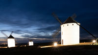view of the historic white windmills of La Mancha above the town of Campo de Criptana at sunset
