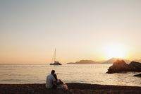 A man and a woman sit hugging on the shore of a calm sea and look at the sailing ship