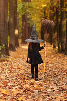 Cute happy little redhaired girl dressed in witch costume standing with broom over autumn forest background