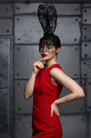 Young woman in black rabbit or hare fancy mask and red dress.