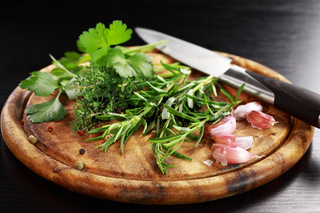 Fresh herbs from garden on wooden platter with knife