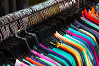 colorful t-shirts hanging on second hand clothing market -