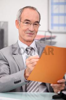 Older man making notes in a file