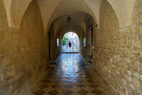 Tourists at a passage at the Cathedral of St. Quirinus in the old town of Krk in Croatia
