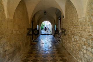 Touristen in einer Passage an der Kirche des heiligen Quirinus in Krk