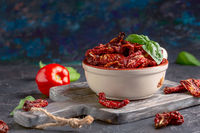 Bowl of dried tomatoes and fresh basil.