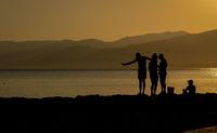 Fishermen silhouette fishing in the coast at sunrice.