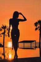 Silhouette of sexy woman in bikini pose near swimming pool