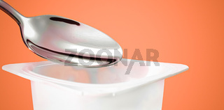 Yogurt cup and silver spoon on orange background, white plastic container with yoghurt cream, fresh dairy product for healthy diet and nutrition balance