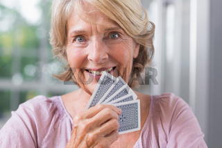 Close up of a happy woman playing cards