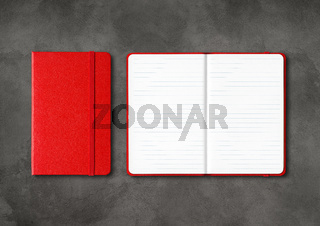 Red closed and open lined notebooks on dark concrete background