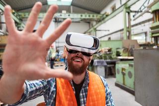 Arbeiter mit VR-Brille tastet in der Virtual Reality Fabrik