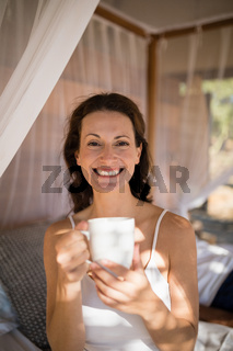 Portrait of happy woman having coffee in canopy bed