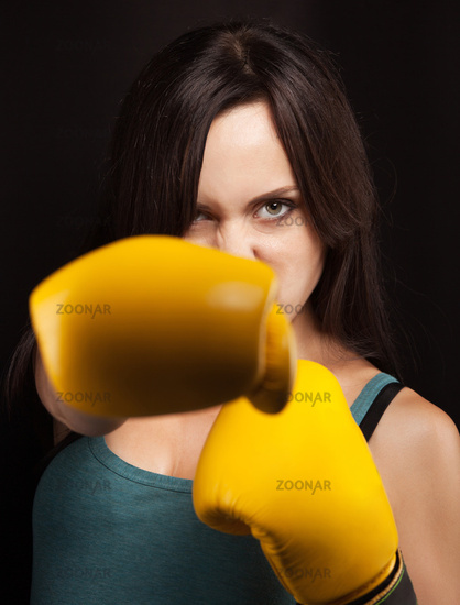 Emotional portrait of a girl in yellow boxing gloves