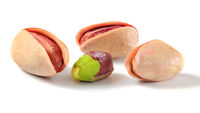 Three roasted Turkish red pistachios, and one partially peeled green nut isolated on white background