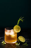 Alcoholic or non-alcoholic cocktail with lime and rosemary on a dark marble table