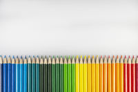 Row of colored pencils on a white sheet of paper