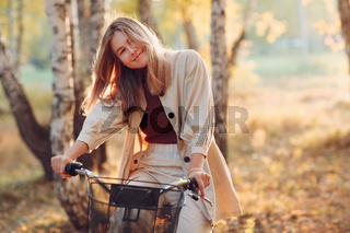 Happy smiling young woman riding vintage bicycle in autumn park at sunset