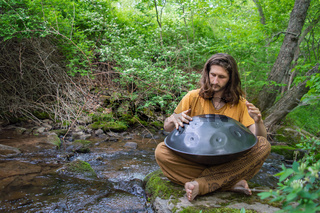 Hippie playing handpan music on the shore of a river
