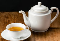 View of white ceramic cup of hot tea and tea kettle.