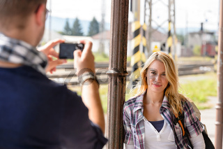 Man taking photograph of woman digital camera