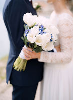 The bride and groom stand hugging and hold a wedding bouquet with white and blue flowers and eucalyptus branches close-up