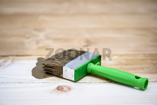 Square cut brush on wooden floor. Toning floor with stain, texture enhancement. Decoration process. Stage before varnishing