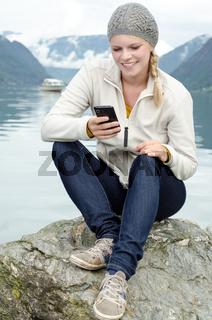 junge blonde Frau mit ihrem Smartphone in der Hand