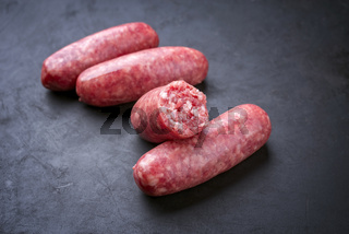 Traditional Italian raw salsiccia fresco meat sausage offered as close-up on a rustic black board