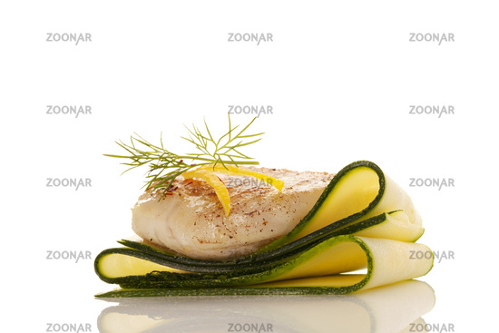 Luxurious seafood dinner. Perch fish fillet on zucchini slices.