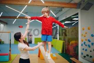 Kids doing balance beam gymnastics exercises in gym at kindergarten or elementary school. Children sport and fitness concept.