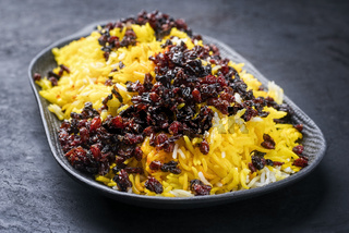 Modern style traditional Persian steamed saffron rice with berberis served as close-up on a cast iron design plate as side dish