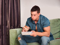 Hungry muscular young man gulping down food sitting on couch