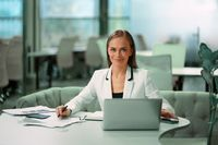 Blond beautiful businesswoman working with documents sitting in front of laptop wearing white official suit. Office worker looking at camera with smile while sitting at her working place