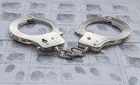 Top view of metal Handcuffs with generic hand prints.