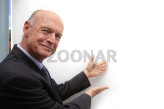 Bald businessman drawing attention to white-board