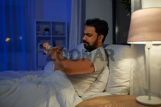 indian man with health tracker in bed at night