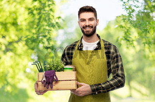 happy gardener or farmer with box of garden tools