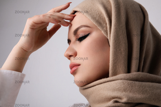 Close-up portrait of young arab muslim woman wearing beige hijab.