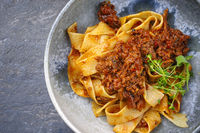 Modern style traditional Italian ragu alla bolognese sauce with papedelle pasta noodles and parmesan cheese served as top view in a ceramic design bowl with copy space left