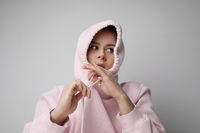 Young woman posing on white background, pulling the hood over the heads.