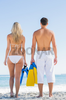 Couple holding flippers and looking at the sea