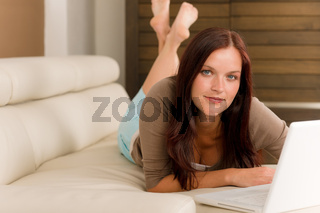 Modern living room woman lying sofa laptop