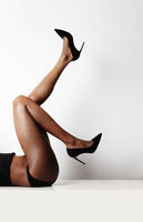 Cropped image of female legs with high heels shoes. Isolated over white wall.