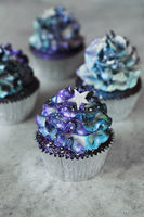 Galaxy colored cupcakes on table