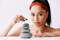 Pretty african american woman doing pyramid of the stones on white background