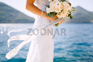 The bride in a white dress holds a beautiful wedding bouquet of roses in her hands on the background of the seascape.