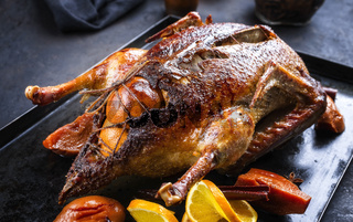 Traditional roasted stuffed Christmas duck with quinces and orange slices served as close-up on a rustic metal tray on a black board