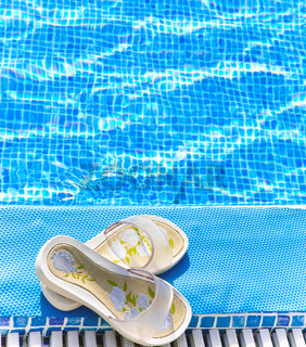 beach slippers on a pool edge